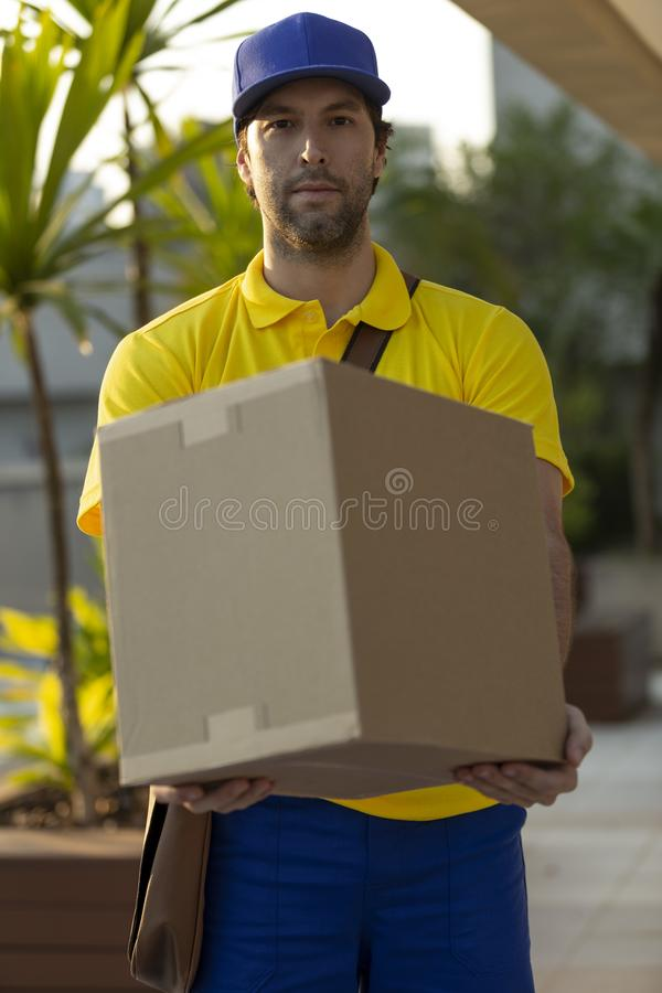 Brazilian mailman delivering a package. On the street. Internet purchase being delivered at home royalty free stock image