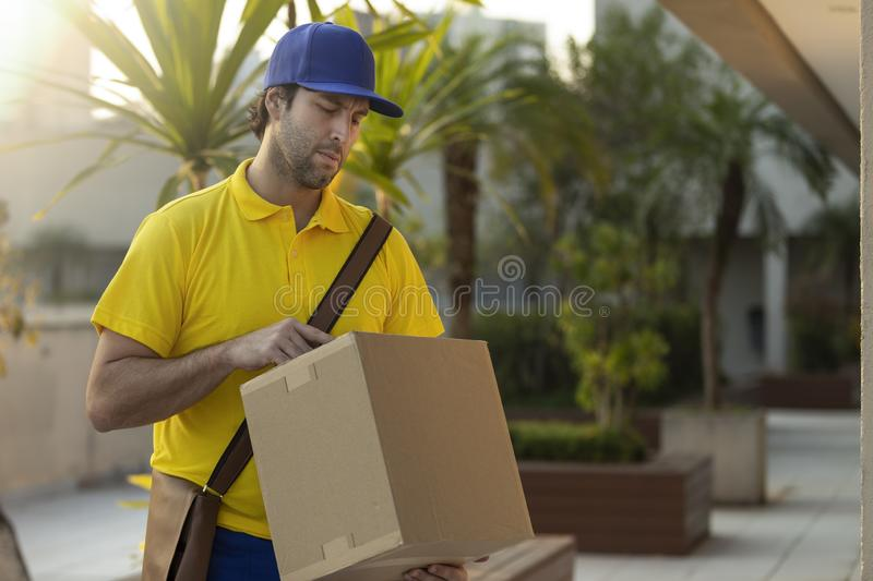 Brazilian mailman delivering a package stock images