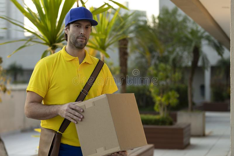 Brazilian mailman delivering a package royalty free stock photo