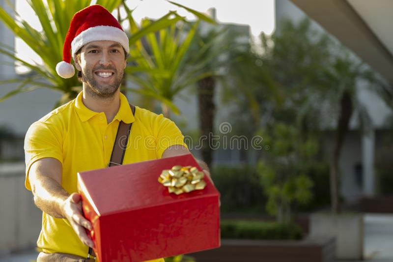 Brazilian mailman dressed as Santa Claus. Delivering a gift. Online purchase being delivered royalty free stock photography