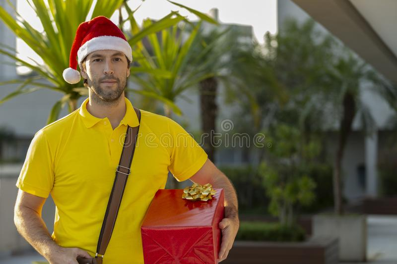 Brazilian mailman dressed as Santa Claus. Delivering a gift. Online purchase being delivered royalty free stock photos