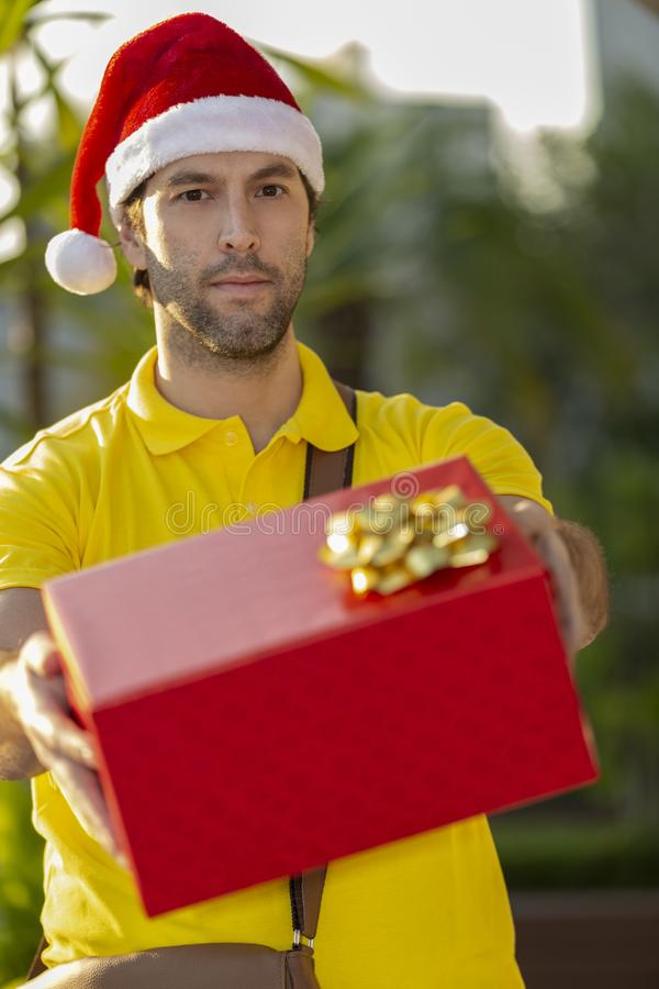 Brazilian mailman dressed as Santa Claus. Delivering a gift. Online purchase being delivered stock photography