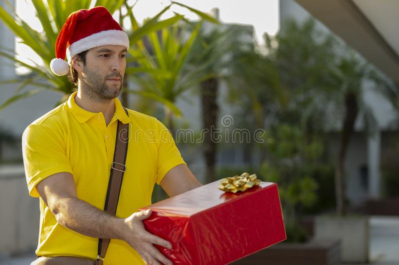 Brazilian mailman dressed as Santa Claus. Delivering a gift. Online purchase being delivered stock images