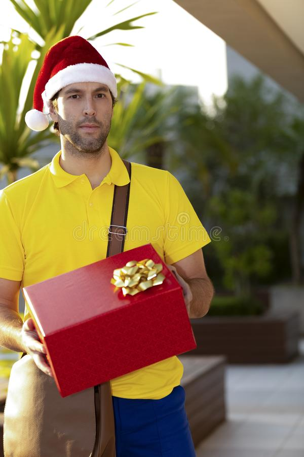 Brazilian mailman dressed as Santa Claus. Delivering a gift. Online purchase being delivered royalty free stock image