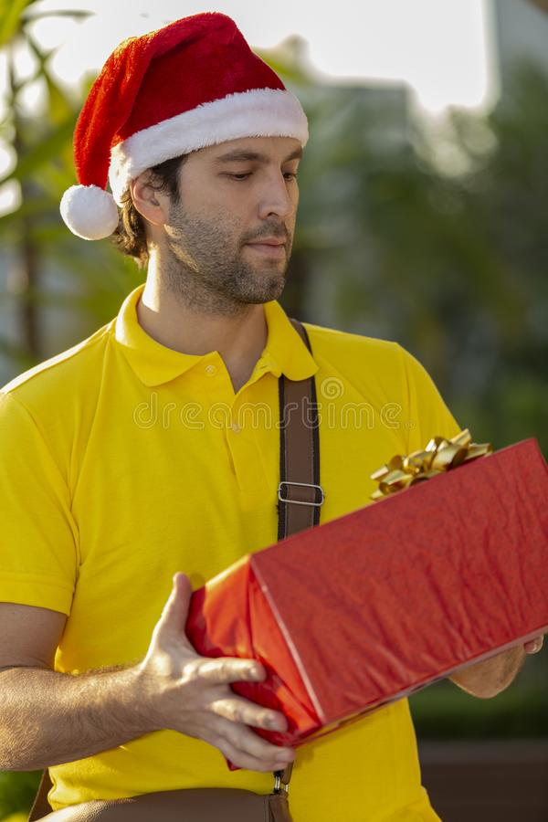 Brazilian mailman dressed as Santa Claus. Delivering a gift. Online purchase being delivered royalty free stock photo