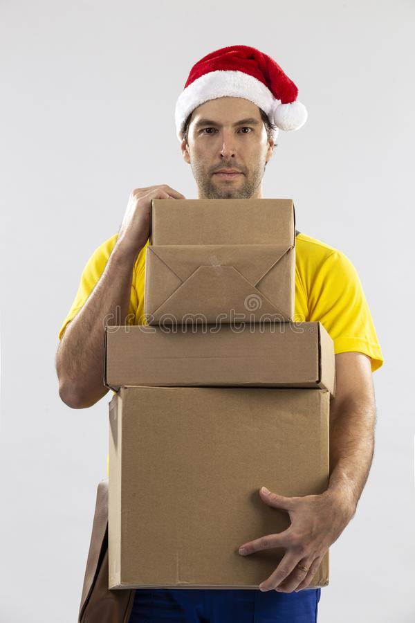 Brazilian mailman dressed as Santa Claus. Delivering a gift on a white background. copy space royalty free stock photography