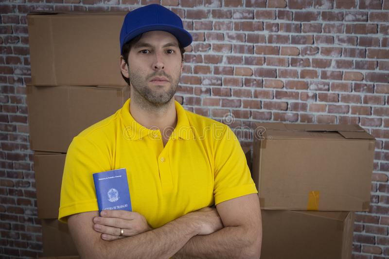 Brazilian mailman holding work book,. Brazilian social security document, in a deposit with a a lot of boxes royalty free stock photo