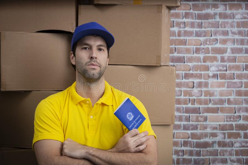 Brazilian mailman holding work book. Brazilian social security document, in a deposit with a a lot of boxes royalty free stock photos
