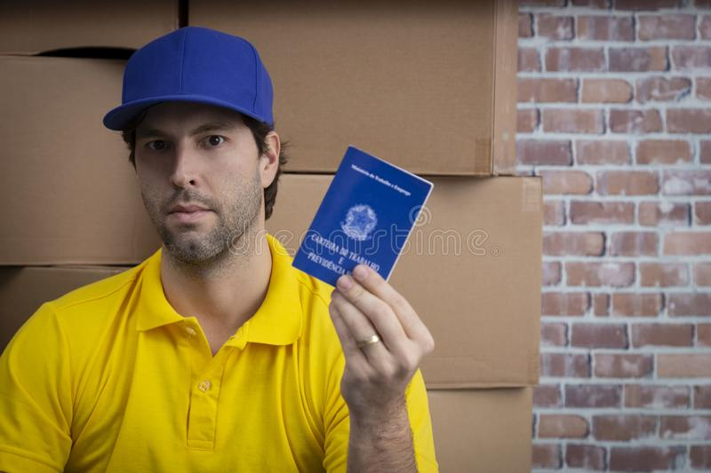 Brazilian mailman holding work book. Brazilian social security document, in a deposit with a a lot of boxes royalty free stock images