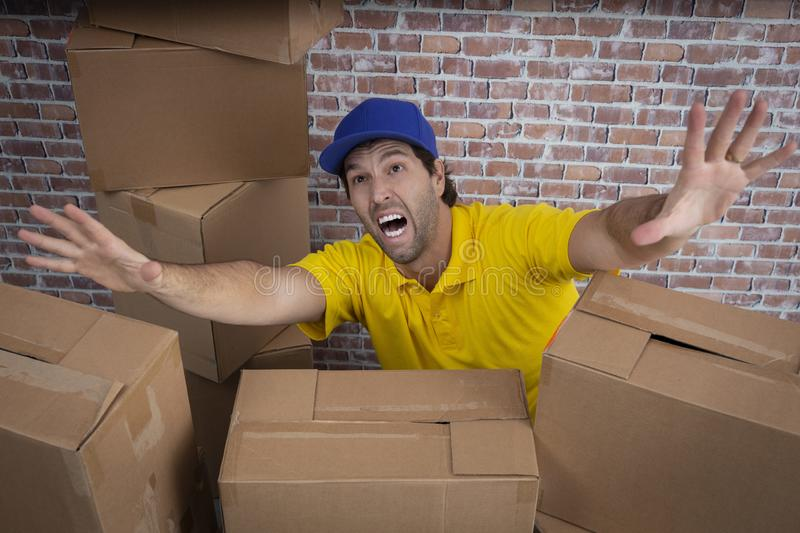 Brazilian mailman lost in a lot of boxes stock photography