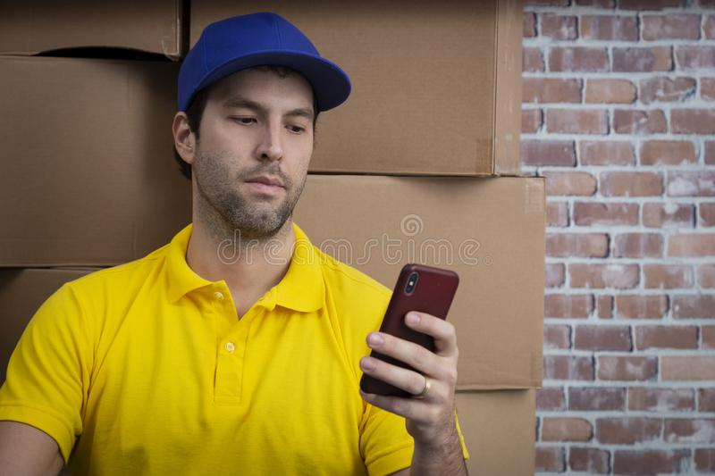 Brazilian mailman using a smartphone in a deposit royalty free stock photography