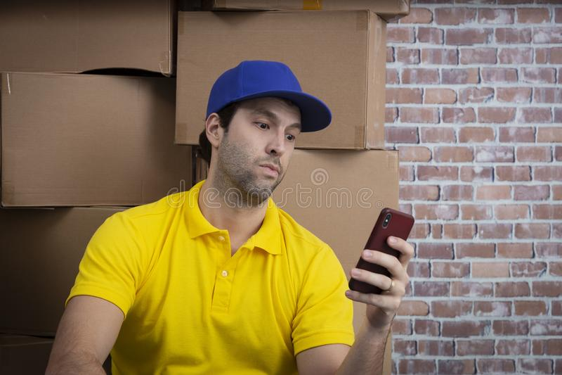Brazilian mailman using a smartphone in front of a lot of packages. Brazilian mailman using a smartphone in a deposit with a a lot of boxes stock photos