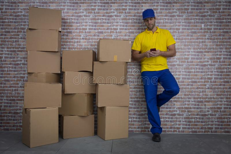 Brazilian mailman using a smartphone in front of a lot of packages royalty free stock photography