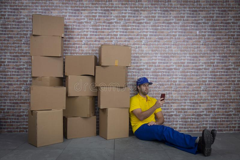 Brazilian mailman using a smartphone in front of a lot of packages. Brazilian mailman using a smartphone in a deposit with a a lot of boxes royalty free stock images