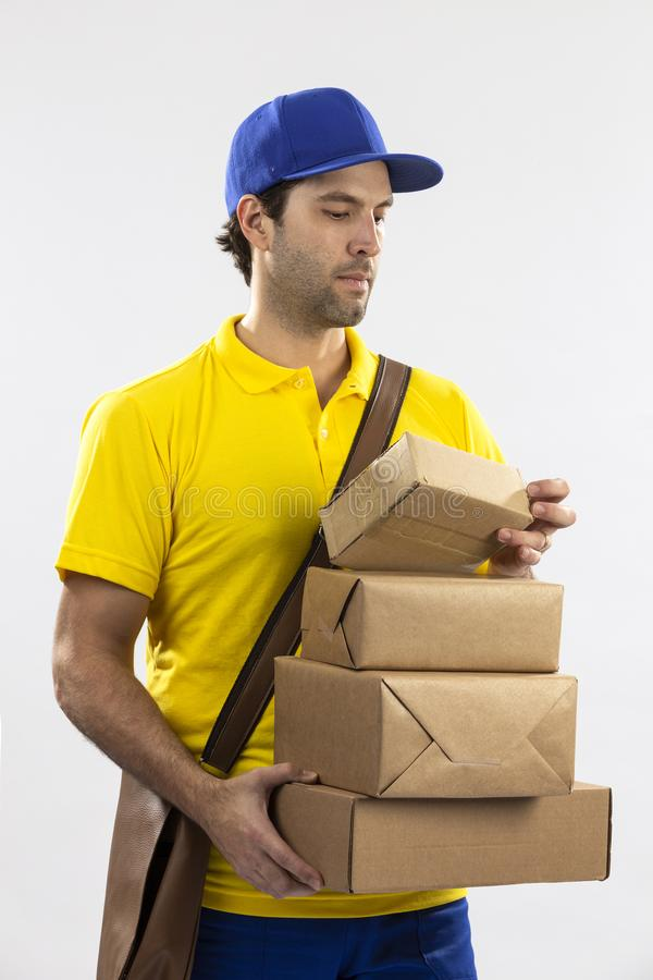 Brazilian mailman on a white background. Delivering a package. copy space royalty free stock image