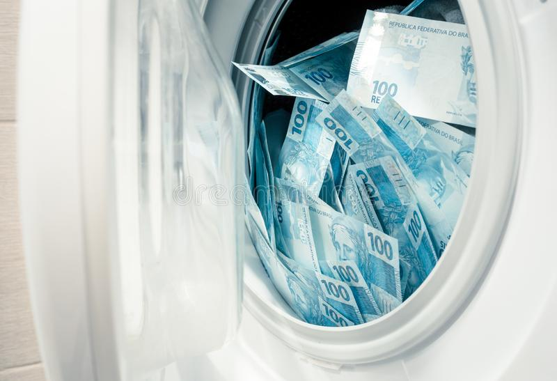 Brazilian money, hundreds of reais in the washing machine.  The concept of money laundering, corruption. Brazil money, hundreds of reais in the washing machine stock image