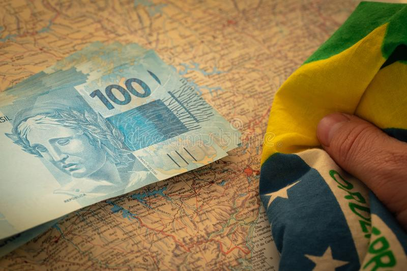 Brazilian money, 100 reais banknote on the map of Brazil and National flag stock photos
