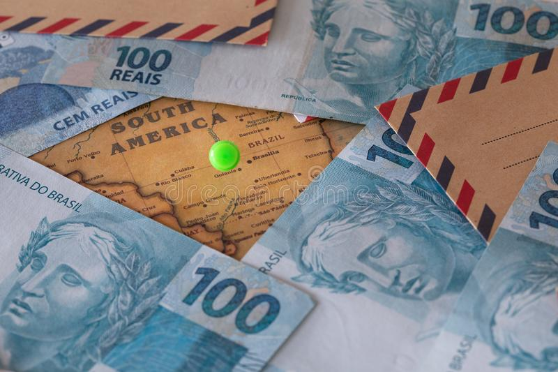 Brazilian money, 100 reais with envelopes lying on a map of South America with a green dot marked, Brazil stock image