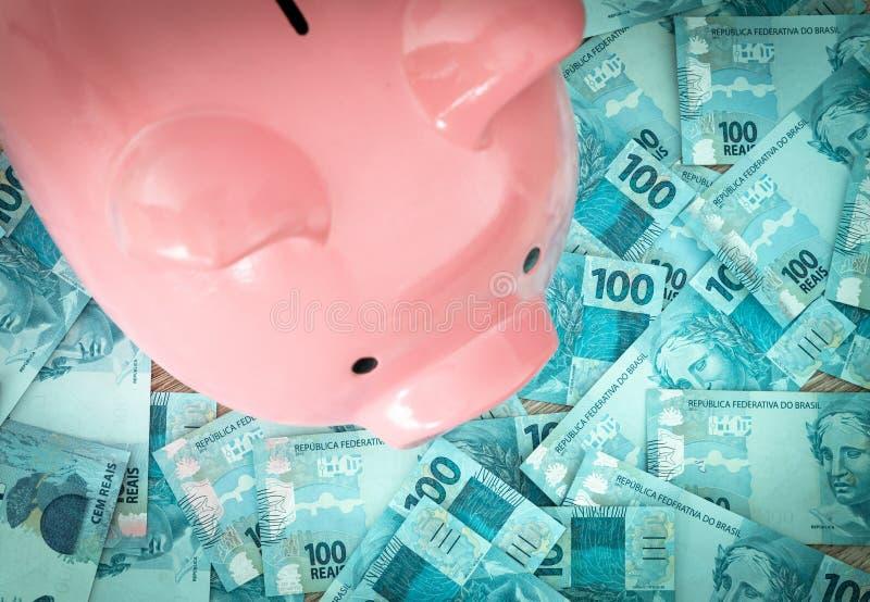 Brazilian money, reais, and piggy bank. Saving and depositing money royalty free stock photography