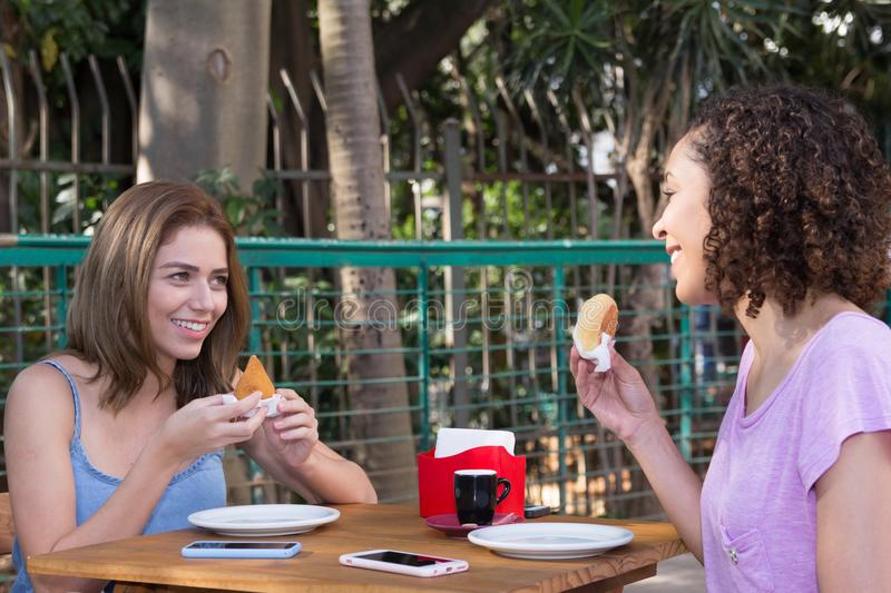 Brazilian girl friends eating pao de queijo and coxinha food snack outdoors in Sao Paulo during summer. stock photography