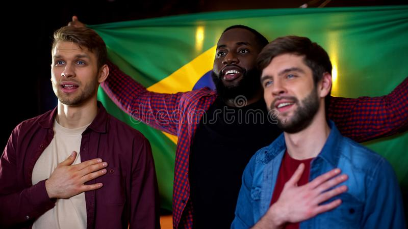 Brazilian multiracial football fans singing national anthem, holding flag in pub. Stock photo stock photography