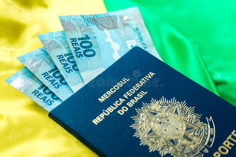 Brazilian passport and brazilian currency (100 Reais) on the table stock images