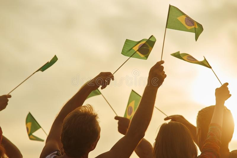 Brazilian patriots with flags outdoor. Silhouette of patriotic brazilian family, rear view royalty free stock photography
