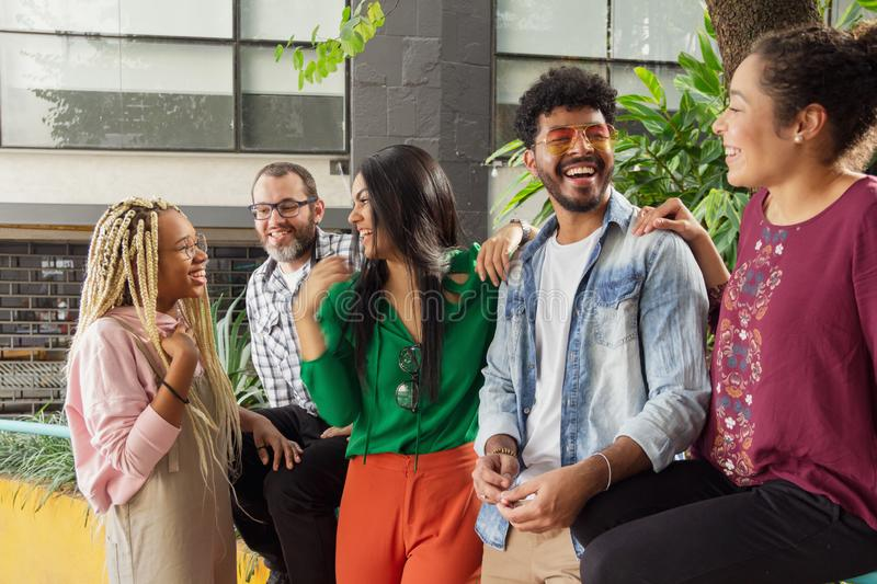 Brazilian people having fun and sitting in the outdoor. Fun and happy times. Diversity and bonding stock photo