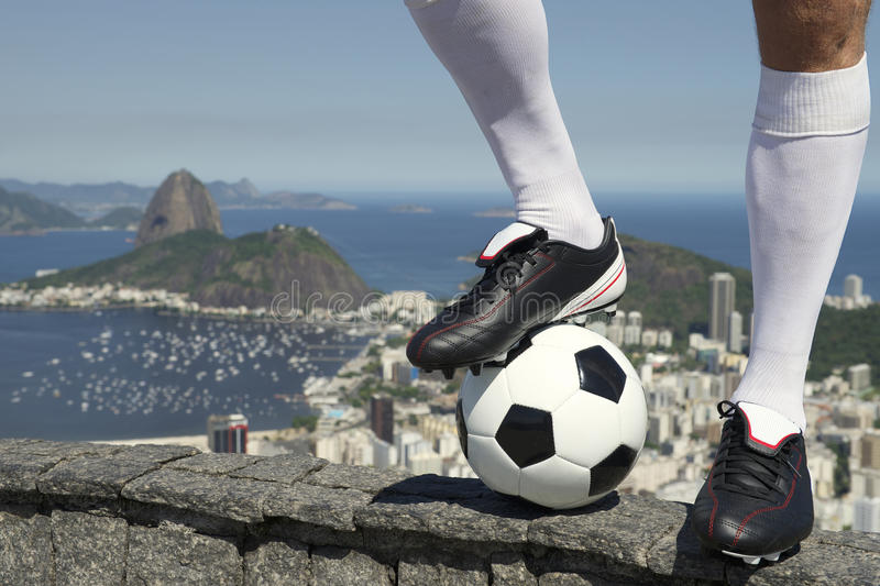 Brazilian Soccer Football Player Standing At Rio Skyline. Feet of Brazilian soccer player standing with football above Rio de Janeiro skyline with Sugarloaf Pao stock photos
