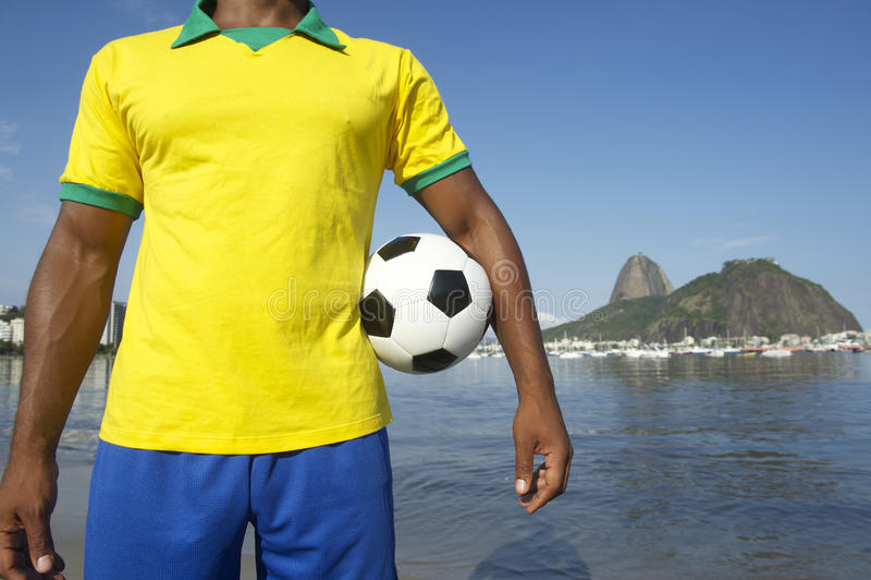 Brazilian Soccer Football Player Wearing Brazil Colors Rio. Brazilian soccer player holding football wearing shirt in Brazil colors at Sugarloaf Pao de Acucar in stock image