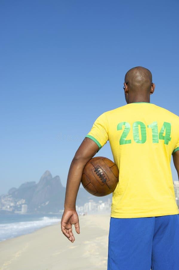 Brazilian Soccer Football Player Wearing 2014 Shirt Rio. Brazilian soccer player wearing 2014 shirt in Brazil colors holding football Ipanema Beach Rio de stock photos