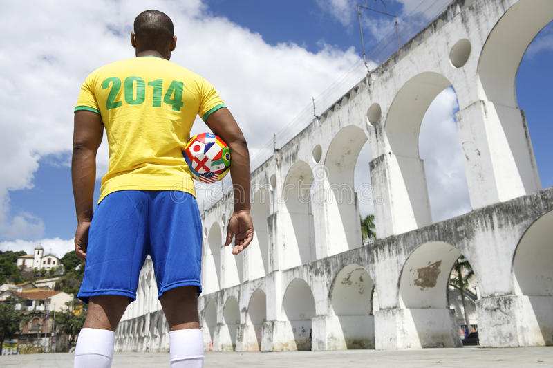 Brazilian Soccer Player 2014 Shirt International Football Rio. Brazilian soccer player holding international football wearing 2014 shirt in Brazil colors Rio de stock photos