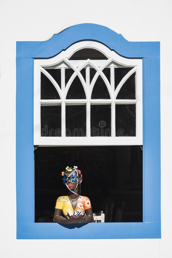 Brazilian souvenir girl at the window, historic town Paraty, Rio de Janeiro state, Brazil royalty free stock photography