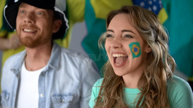Brazilian supporters watching football match on tv, celebrating team victory. Stock photo stock image