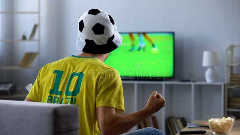 Brazilian team supporter actively cheering favourite football team, match on tv. Stock photo stock image