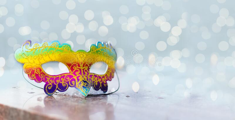 Brazilian or Venetian carnival.Bright multicolored mask on a bright shiny background with lights and bokeh.holiday.Carnival outfit. Celebration.Banner.Flat lay royalty free stock photo