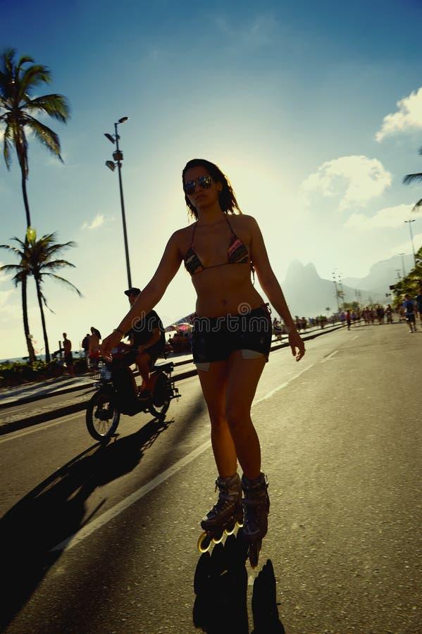 Brazilian Woman Skating Rio de Janeiro Brazil. RIO DE JANEIRO, BRAZIL - FEBRUARY 2, 2014: Young Brazilian woman skates along the beachfront road on a car-free stock photography