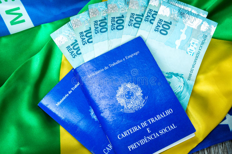Brazilian work document and social security document (Carteira de Trabalho) and brazilian currency (Reais) on brazilian flag royalty free stock images