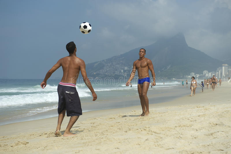 Brazilians Playing Altinho Beach Football Rio de Janeiro Brazil. Two young carioca Brazilians playing altinho keepy uppy beach football at Posto 9 on Ipanema royalty free stock photography