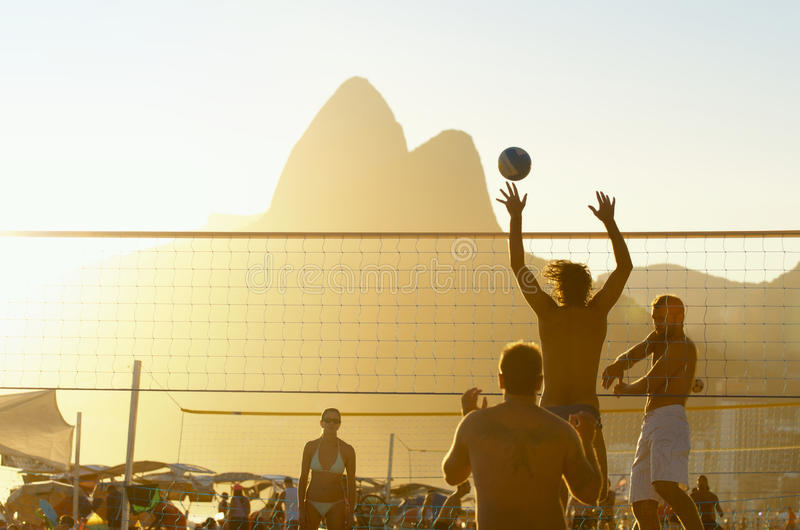 Brazilians Playing Beach Volleyball Rio de Janeiro Brazil Sunset. RIO DE JANEIRO, BRAZIL - FEBRUARY 01, 2014: Young Brazilians play a game of beach volleyball