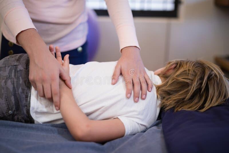 Brazo de examen del terapeuta de sexo femenino del muchacho que miente en cama imagenes de archivo