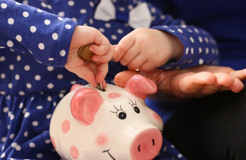 Brazo de la ni?a del ni?o que pone monedas en piggybank imagen de archivo libre de regalías