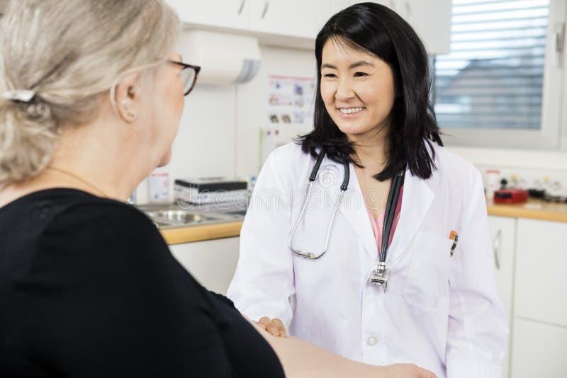 Brazo del doctor Touching Senior Patient sonriente antes del análisis de sangre fotografía de archivo