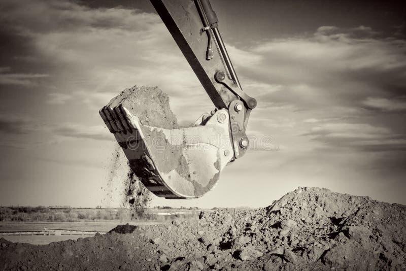 Brazo del excavador y suciedad de excavación de la cucharada en el emplazamiento de la obra fotos de archivo libres de regalías