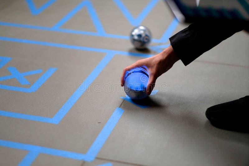 Brazo del jugador con un bal del robot foto de archivo