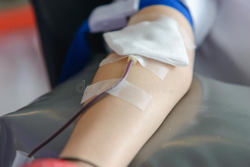 Brazo derecho del varón asiático que recibe sangre y que sostiene la bola de goma a disposición Atención sanitaria y caridad Dona imagen de archivo libre de regalías