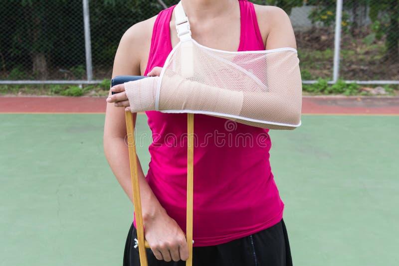 Brazo doloroso herido de la ropa de deportes de la mujer que lleva con el vendaje de la gasa, fotografía de archivo libre de regalías
