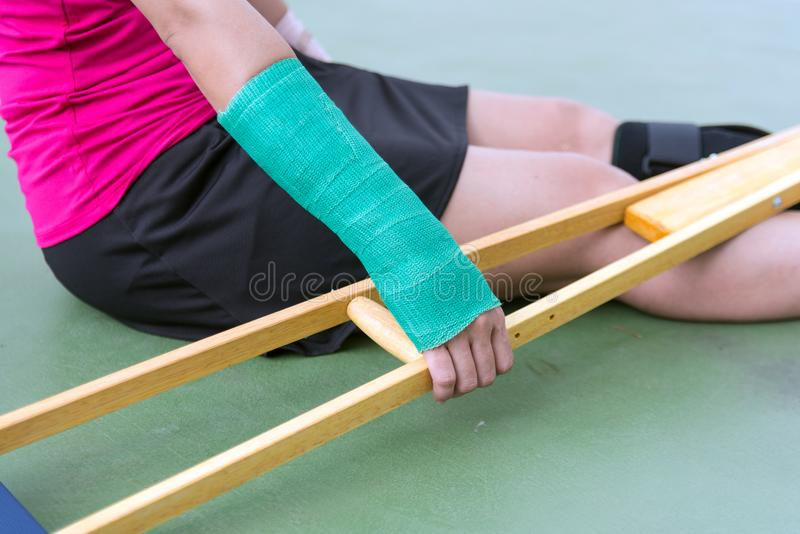 Brazo doloroso herido de la ropa de deportes de la mujer que lleva con el vendaje de la gasa, el molde del brazo y las muletas de fotos de archivo libres de regalías