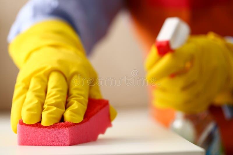 Brazo en el guante protector del látex amarillo que limpia del polvo imagen de archivo libre de regalías