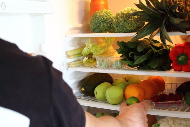 Brazo humano que alcanza para la fruta de la cal en refrigerador abierto por completo fotos de archivo libres de regalías